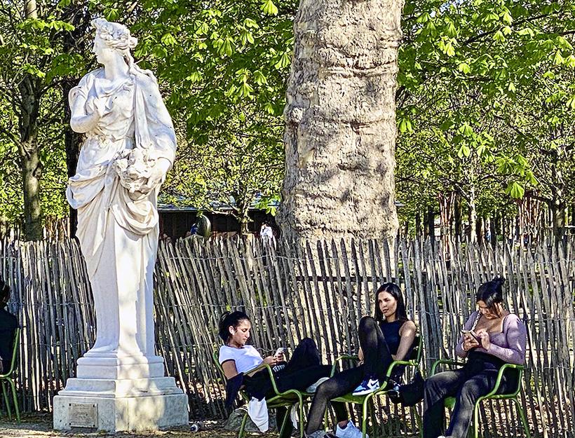 Classical marble statue, three modern women friends relax, Jardin des Tuileries